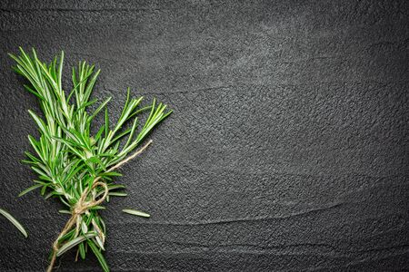 Fresh rosemary branches on black stone background. Top view with copy space.