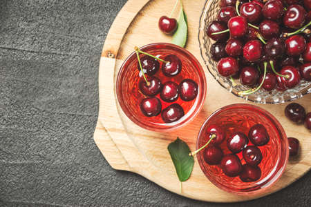 Close-up photo of fresh juice with sweet cherries on black concrete table, top view with copy space.