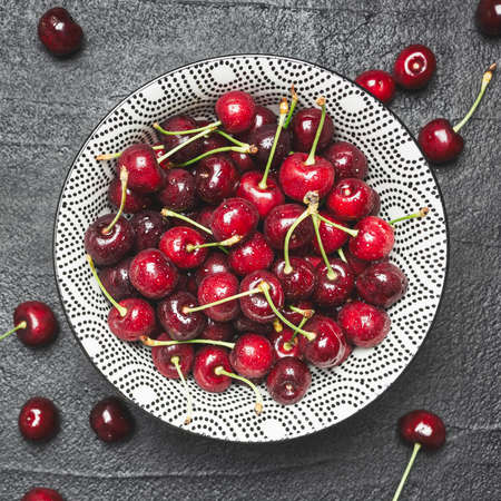 Juicy ripe cherries with water drops in ceramic bowl on black concrete table, top view.