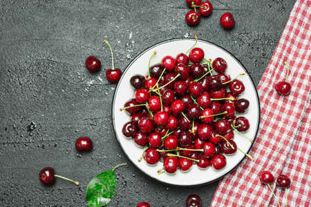 Fresh sweet cherries bowl on black concrete background, top view with empty space.