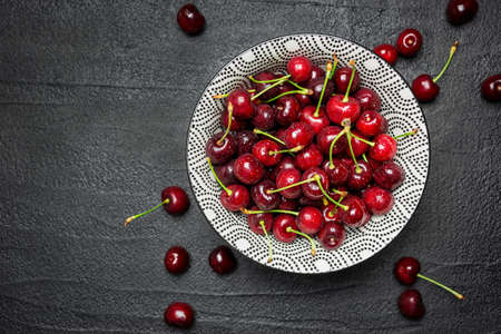 Juicy ripe cherries with water drops in ceramic bowl on black concrete table, top view with empty space.