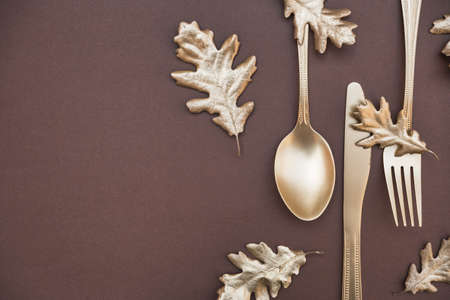 Golden colored leaves and cutlery on dark brown background. Creative autumn table setting. Flat lay, top view, copy space.