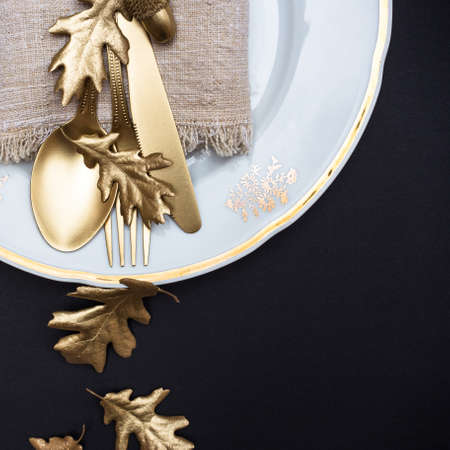 Golden colored leaves and cutlery on black background. Creative autumn table setting. Flat lay, top view, copy space. 免版税图像