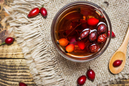 Cup of tea with rose hips on rustic background, top view, close-up. Autumn vitamin drink. Standard-Bild