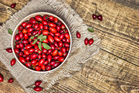 Fresh ripe rose hips in bowl on the rustic background, close-up photo. Healthy nutrition concept.