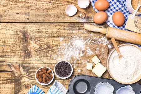 Frame of baking and cooking pastry or cake with ingredients and utensils. Flour, sugar, eggs, butter and almonds on rustic wooden background with copy space for text, flat lay.