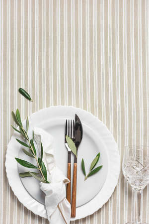 Festive table setting with white plate, cutlery and decoration with olive branches. Beautiful flat lay arrangement.