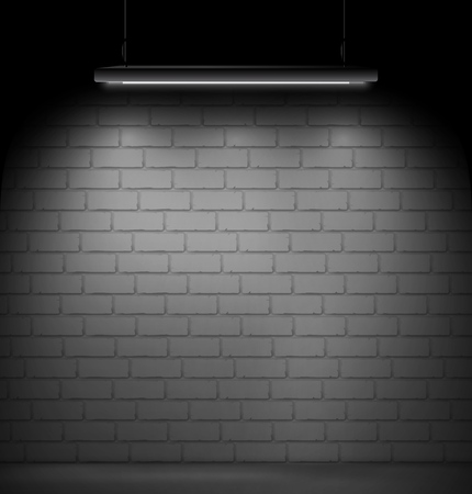 Dark room with a brick wall on the background and fluorescent lamp light.