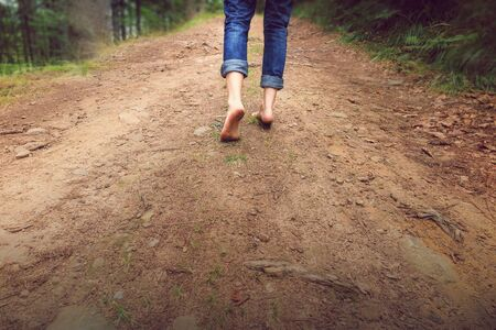 Person walking barefoot on gravel muddy road in mountains. Hiking and walking fast. Healthy life style with dirty feet Stock Photo
