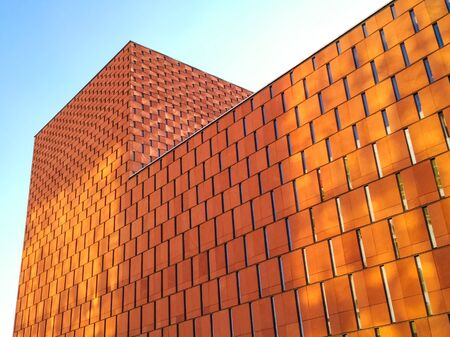 Abstract modern architecture with bright orange buildings facade made of panels and windows creating abstract composition,
