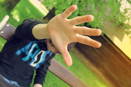 Shy man covering his face against camera. Man using hand to protect against sun on sunny day. Focus on hand with boy and nature in background.