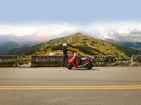 Girl in a helmet with her red scooter parked on a side road enjoying beautiful view of high mountains scenery. Travel and explore the world on motorbike. Adventurous girl with backpack on scooter on a road trip Stock Photo