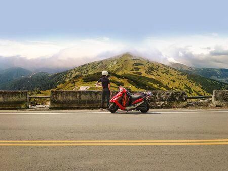 Mädchen in einem Helm mit ihrem roten Roller, der auf einer Seitenstraße geparkt ist und einen schönen Blick auf die Hochgebirgslandschaft genießt. Reisen und erkunden Sie die Welt mit dem Motorrad. Abenteuerliches Mädchen mit Rucksack auf Roller auf einem Roadtrip