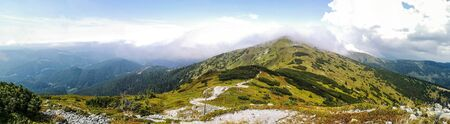 Wide panorama photo of high grassy mountains surrounded by misty white clouds. Yellow grass with greenery.