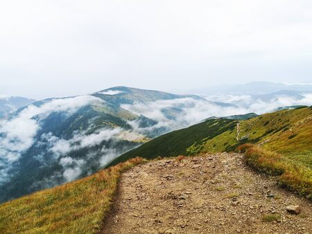 Scenery of beautiful high mountains with greenery. Mountain ridge path for hiking and trekking. View surrounded by clouds and mist in high altitude.
