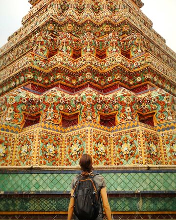 Back view of traveling girl looking up at colorful ancient temples in Thailand