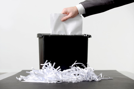 종이 분쇄기에 문서를 넣어 사업가의 손 스톡 콘텐츠