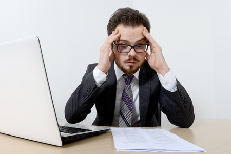 Worried young businessman with laptop and documents Stock Photo