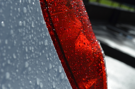 motor de carro: Gotas de lluvia en los faros de un coche rojo