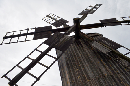 abandoned house: Blades of  wooden windmill against the sky