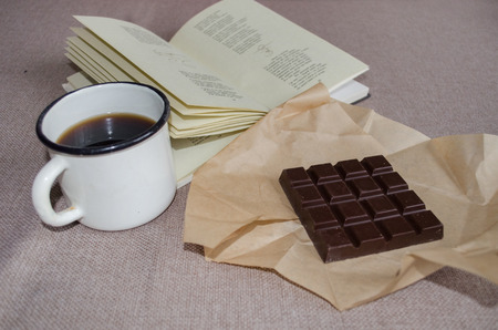 poems: Bar of dark chocolate, mug of coffee and a book of poems Stock Photo