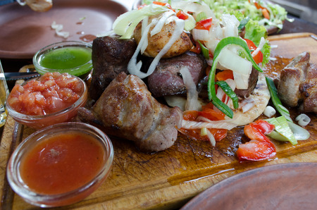 barbecue meat on a wooden board with vegetables and souses