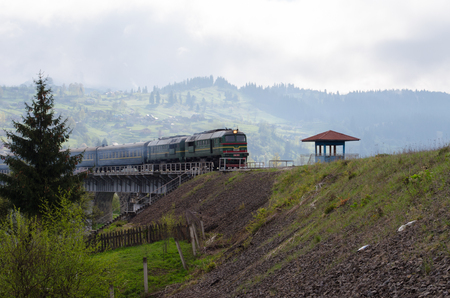 diesel train traveling on the bridge over the mountain village