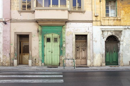 faade: Green and yellow building faade with four doors, in Malta.