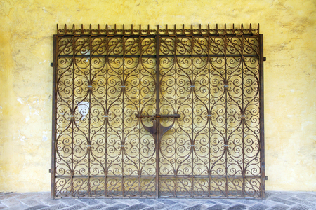 leaned: Iron gates leaned on a yellow wall in a monastery in Barcelona, Spain. Stock Photo