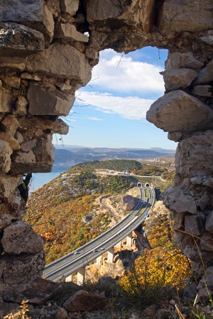 viewed: Highway bridge and tunnel through autumn scenery viewed through a hole in a castle wall Croatia. Editorial