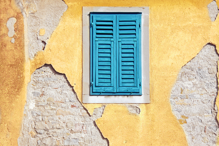faade: Peeling paint on a yellow house faade with a blue window.