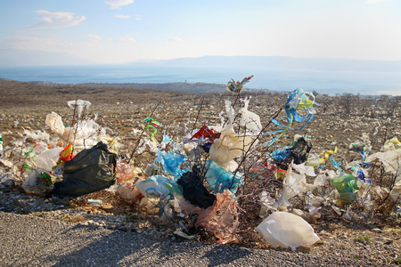 polluting: Discarded plastic shopping bags from an unguarded garbage disposal facility, polluting meadows on a hill slope in Croatia.