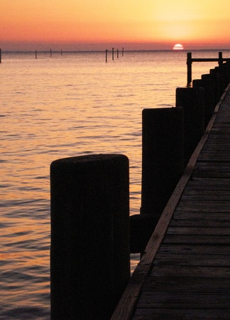 Watching the sun set on the dock of the bay. Stock Photo