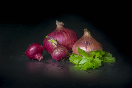 spiciness: onion decorated parsley leaves on Black background Stock Photo
