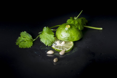 spiciness: Lime decorated parsley leaves on black background