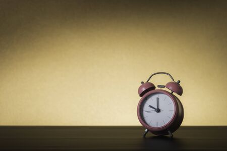 Pink alarm clock on a Brown background. Time concept.