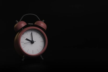 Pink alarm clock. on a Black background. Time concept.