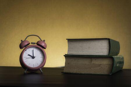 El estudio arduo simbólico es poderoso para tener éxito, concepto con libro y reloj despertador. Tiempo en el negocio y calidad Foto de archivo