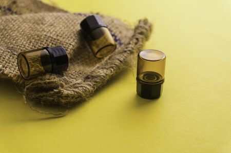 Composition of bottles for aroma, essential oil or medicine on a yellow background in other perspective. Soft focus in the middle.
