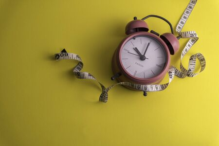Clock with a measuring tape, diet or healthy eating concept. Soft focus in middle Stockfoto