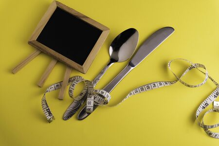 Black Board, spoon and knife  with a measuring tape, diet or healthy eating concept