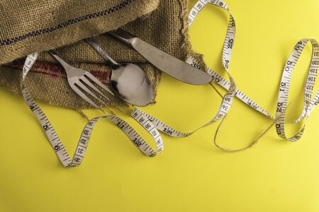 Fork, spoon,knife and measurement tape with yellow background, diet or healthy eating concept. Soft focus at the middle.