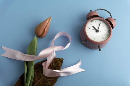 Breast cancer concept with ribbon, time and pink flower isolated by blue back ground. Banco de Imagens - 132480732