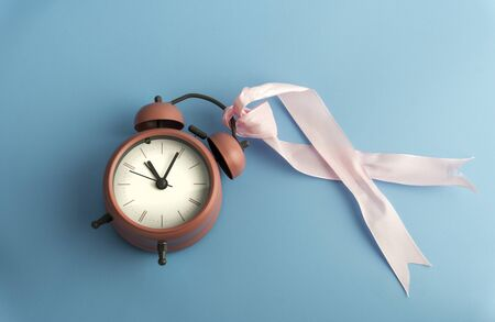 Breast cancer concept with ribbon, time and pink flower isolated by blue back ground. Banco de Imagens