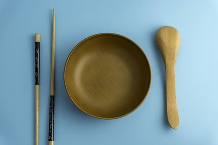 Wooden spoon, and bowl isolated on blue background.