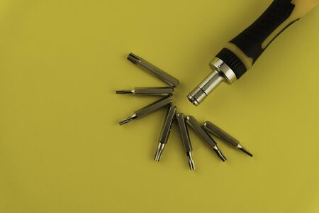 Interchangeable screwdriver set with different types of metal steel heads and bits. Isolated on white background.