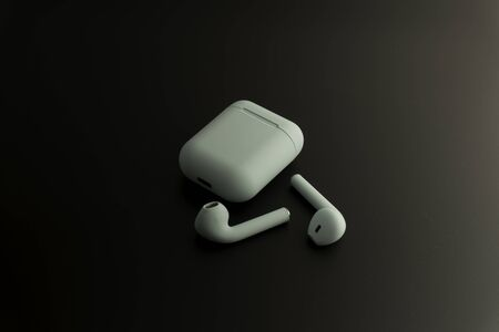 wireless earphones or headphones, plastic case or box for storage and charging and smartphone on black background, close up