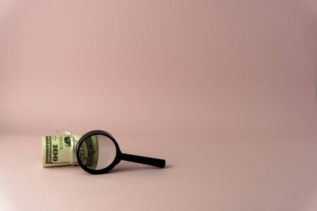 USD upon closer inspection with a magnifying glass becomes 100 USD, isolated on pink background 스톡 콘텐츠