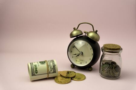 Time to make money concept, pink retro styled alarm clock on heap of american dollars. Banking, Savings, Wealth.