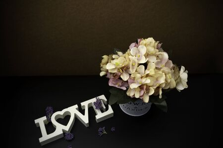 Flowers with word Love on wooden planks background, empty space for text and love concept. 写真素材